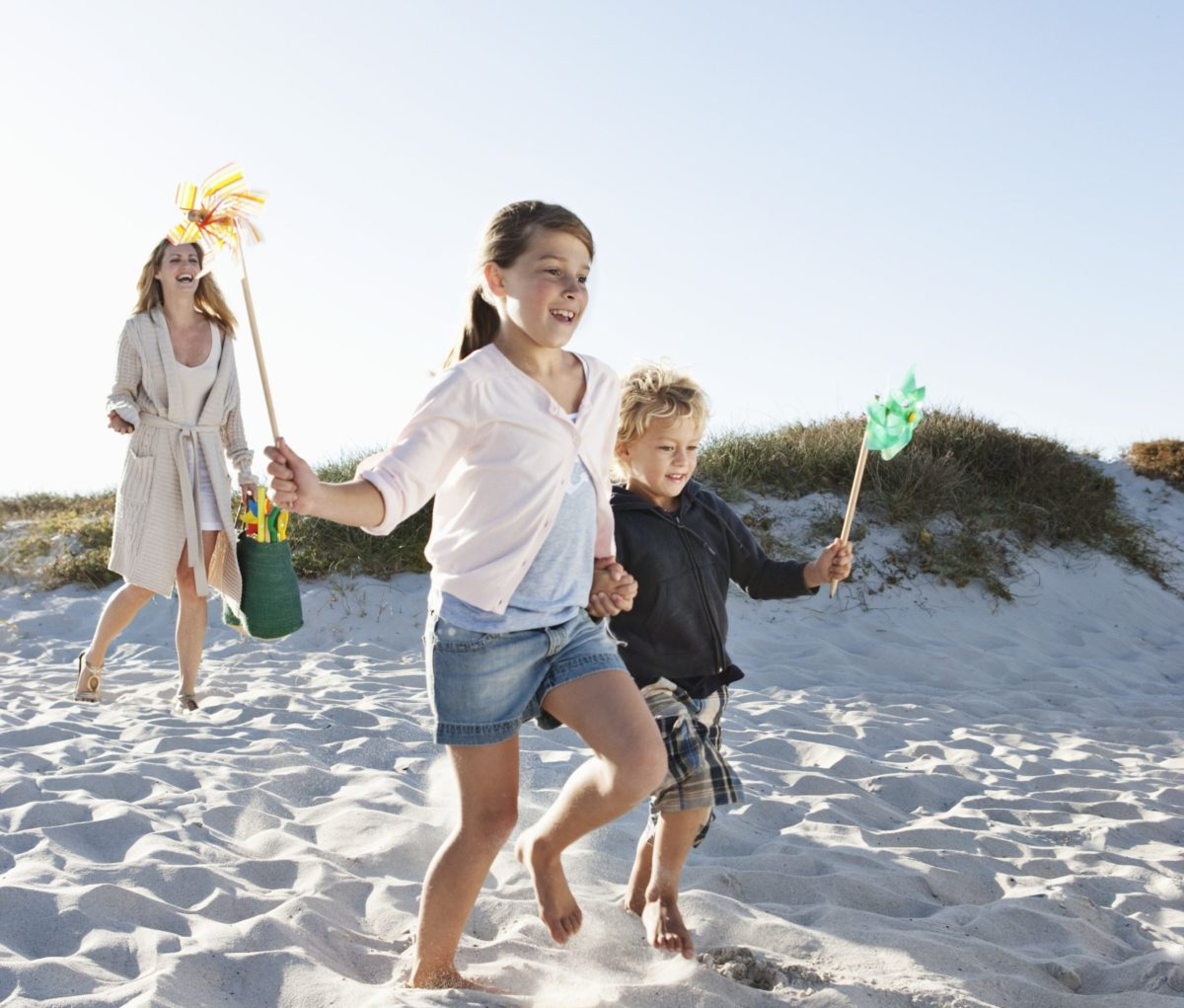 Boy (7-9) and girl (10-12) with mother running on sand dune and holding pinwheel --- Image by © Felix Wirth/Corbis