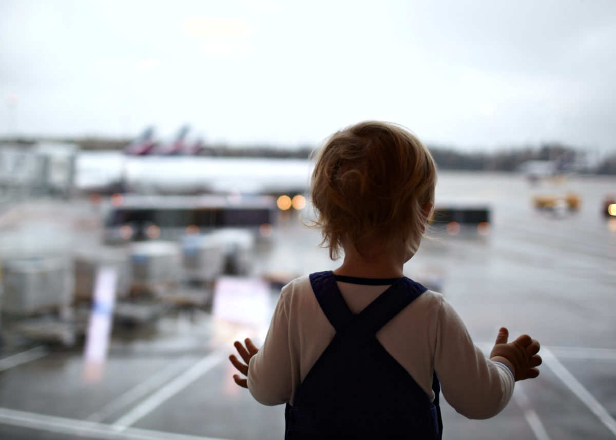 Two year old babyboy is looking at the planes in the airport.